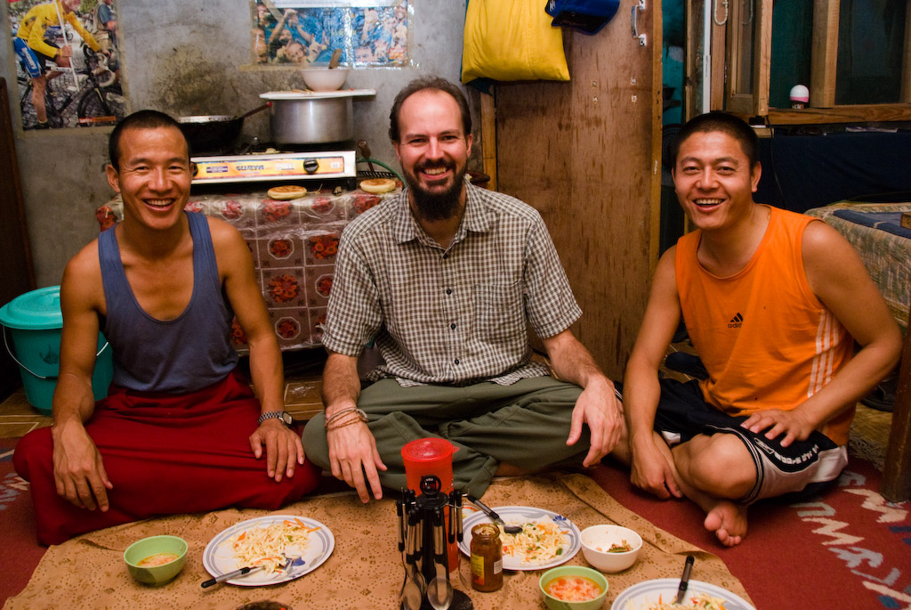 Jon having a meal with Tibetan monks in India